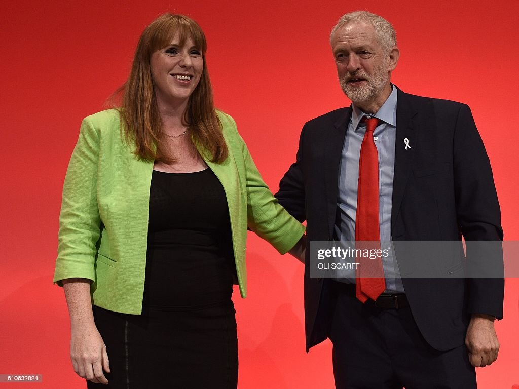 British Shadow Education Secretary, Angela Rayner (L) stands with Leader of the opposition Labour Party Jeremy Corbyn on stage on the third day of annual Labour Party conference in Liverpool, north west England on September 27, 2016. Distracted by a bitter leadership contest, Britain's main opposition Labour party has struggled to present a vision of Brexit to challenge the ruling Conservatives -- and many fear the re-election of Jeremy Corbyn will do little to change this. / AFP / Oli SCARFF
