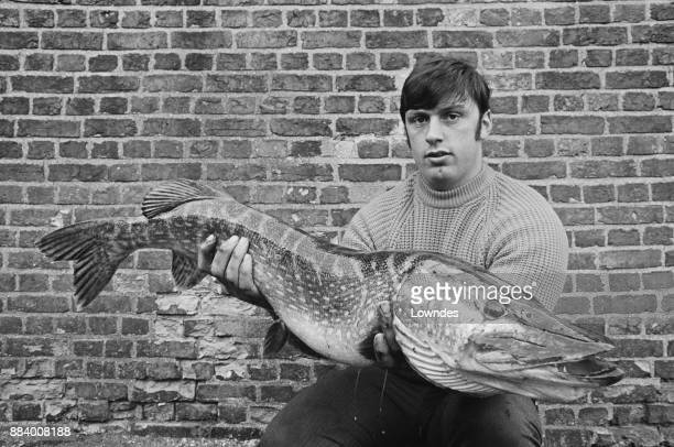 British shot putter and professional Highland Games competitor Geoff Capes holding a large pike UK 27th March 1971