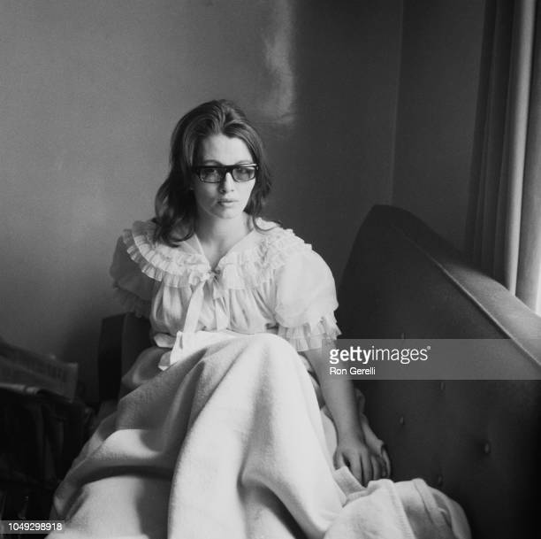 British showgirl and fashion model, Christine Keeler , known for her role in the Profumo Affair, pictured wearing a nightdress lying on a sofabed at...