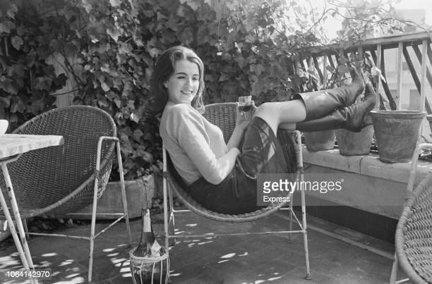 British showgirl and fashion model, Christine Keeler , known for her role in the Profumo Affair, pictured seated on a patio chair holding a glass of...