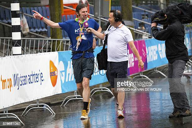 British Simon Brownlee talks to a journalist as he crosses the finish line of the fourth and final day of the 100th edition of the International Four...