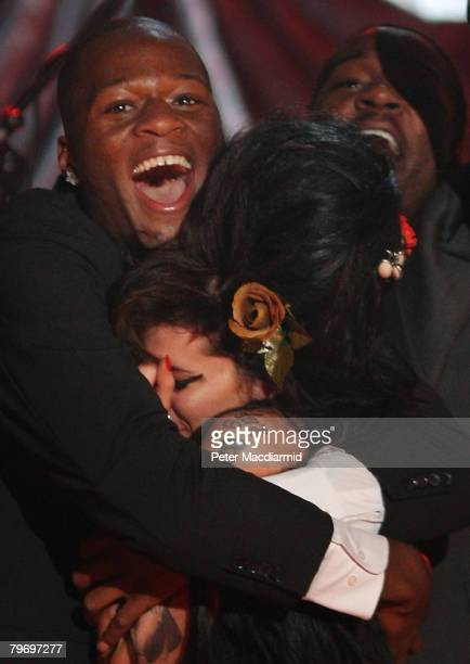 British singer Amy Winehouse is hugged by band member Zalon at The Riverside Studios for the 50th Grammy Awards ceremony on February 10 2008 in...