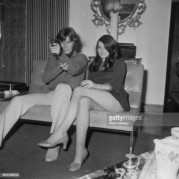 British singer and songwriter Barry Gibb pointing a gun while sitting next to his girlfriend former Miss Edinburgh Linda Gray UK 19th October 1968