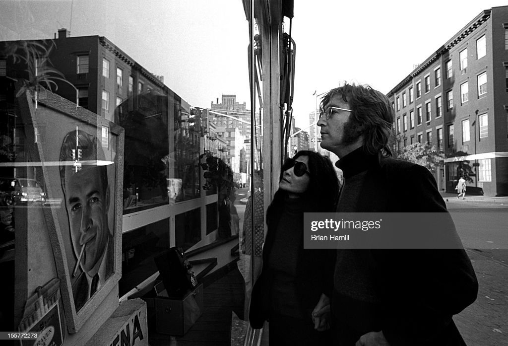 British singer and songwriter John Lennon (1940 - 1980) and his wife, Japanese-born musician and artist Yoko Ono, look in a window display in their neighborhood, around Bank Street in Greenwich village, New York, New York, October 1972.