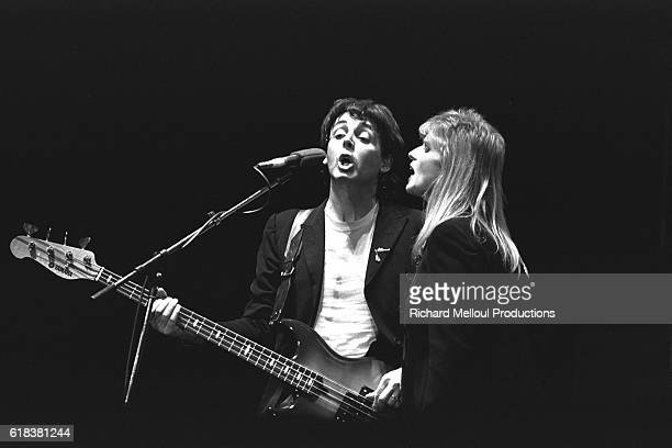 British singer and songwriter Paul McCartney performing on stage with wife Linda