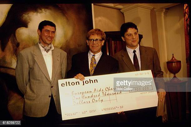British singer and songwriter Sir Elton John gives a cheque to the antiAIDS fight