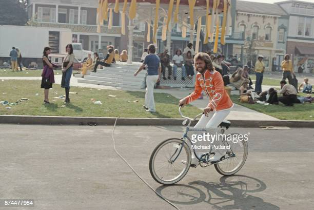 British singer Barry Gibb of pop group The Bee Gees riding a bicycle on the set of 'Sgt Pepper's Lonely Hearts Club Band' musical comedy film...