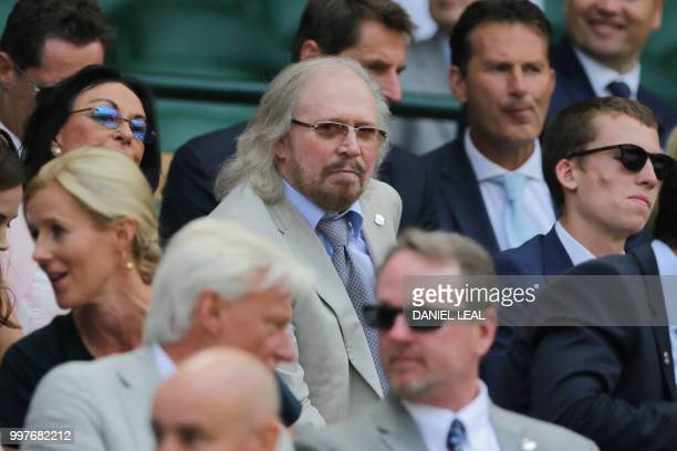 British singer Barry Gibb takes their seat in the Royal box on Centre Court to watch US player John Isner play South Africa's Kevin Anderson during...
