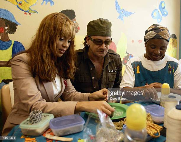 British singer Bono and American singer Beyonce Knowles visit the Baphumele childrens home in the township area of Khayelitsha prior to the Give 1...