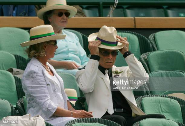 British singer Cliff Richard adjusts his hat as he looks semi-final tennis match of the 2008 Wimbledon championships between US Venus Williams and...