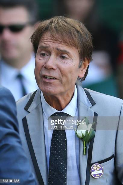 British singer Cliff Richard greets another guest in the royal box on centre court before the men's singles quarterfinal match between Switzerland's...