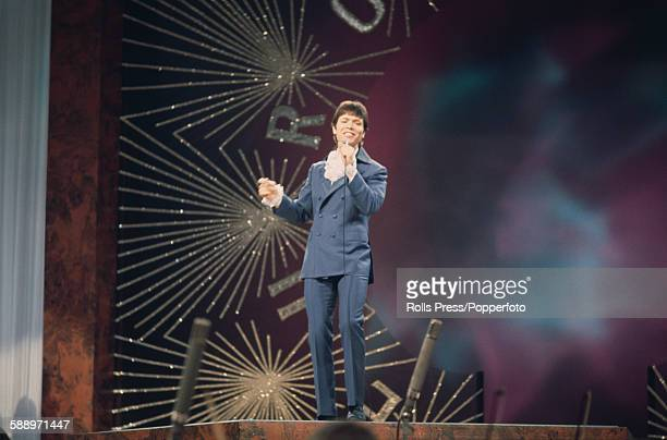 British singer Cliff Richard pictured performing on stage during the Eurovision Song Contest held at the Royal Albert Hall in London on 6th April...