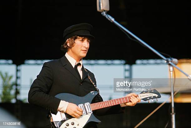 British singer composer and musician John Lennon playing guitar and singing during the concert of British band The Beatles at the Velodromo Vigorelli...