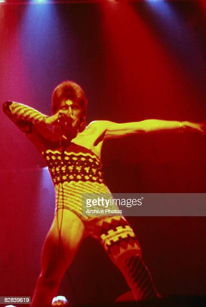 British singer David Bowie performs onstage wearing makeup and a costume that covers only one leg and one arm 1973