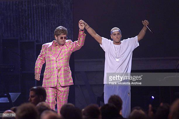 British singer Elton John and American rap vocalist Eminem hold hands after their performance at The 43rd Annual Grammy Awards held at Staples Center...