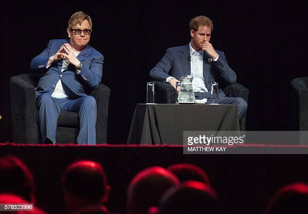 British singer Elton John and Britain's Prince Harry attend the International Aids Conference at the international convention centre in Durban on...