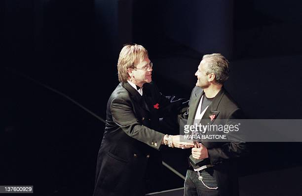 British singer Elton John presents Italian designer Gianni Versace with the 1992 Council of Fashion Designers of America International Award at the...