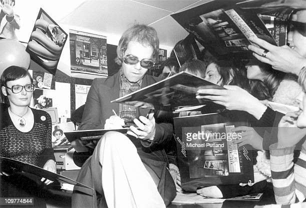 British singer Elton John signing copies of his record 'Don't Shoot Me I'm Only the Piano Player' at Noel Edmond's Record Bar in the King's Road...