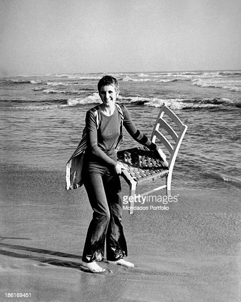 British singer Julie Driscoll raising a chair by the seashore 1960s