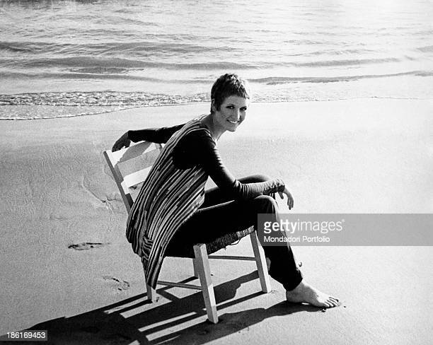 British singer Julie Driscoll smiling on a chair by the seashore 1960s