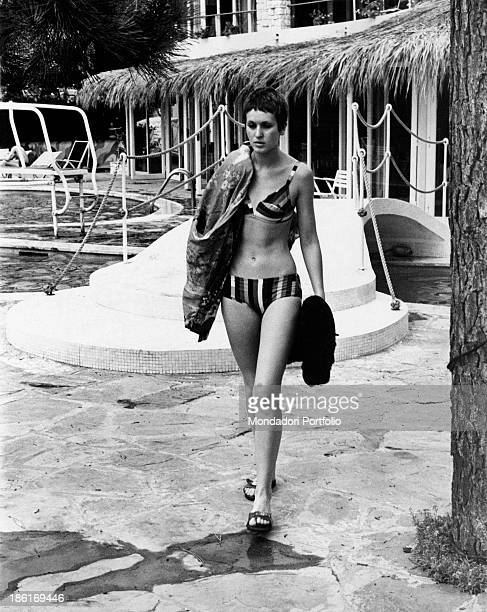 British singer Julie Driscoll walking in swimsuit along the edge of a swimming pool 1968