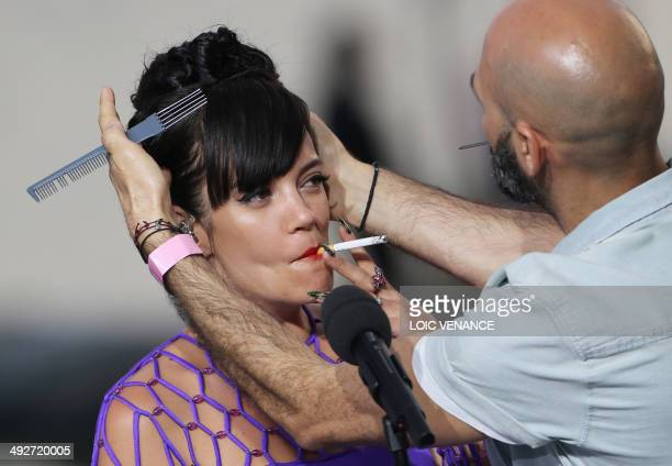 British singer Lily Allen smokes a cigarette as she gets ready to perform on the set of the French TV channel Canal Plus on the sidelines of the 67th...