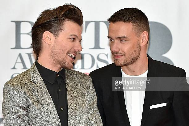 British singer Louis Tomlinson and British singer Laim Payne from the band One Direction pose on the red carpet after arriving to attend the BRIT...