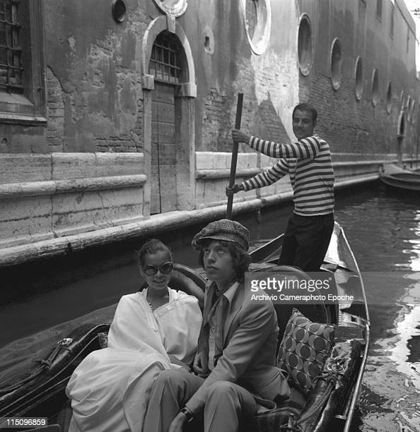 British singer Mick Jagger wearing a suit sitting next to Bianca Jagger wearing a white poncho and sunglasses in a gondola with the gondolier behind...