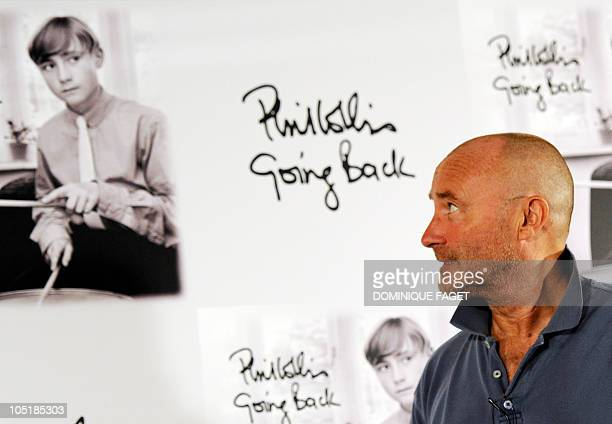 British singer Phil Collins looks at a picture of himself duing a photocall for the presentation of his new album 'Going back' in Madrid on September...