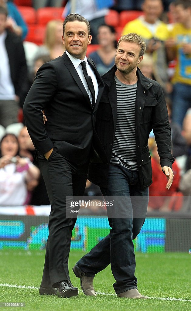 British singer Robbie Williams (L) and former 'Take That' band mate Garry Barlow pose on the pitch before the Unicef Soccer Aid charity football match at Old Trafford in Manchester, north-west England on June 6, 2010. Soccer Aid is the brainchild of Robbie Williams and all money raised through profits from ticket sales and donations made by viewers of ITV during the match will go to UNICEF�s invaluable work helping children around the world.
