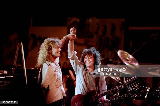 British singer Robert Plant holds hands raised high with British guitarist Jimmy Page during a Led Zeppelin reunion performance at Madison Square...