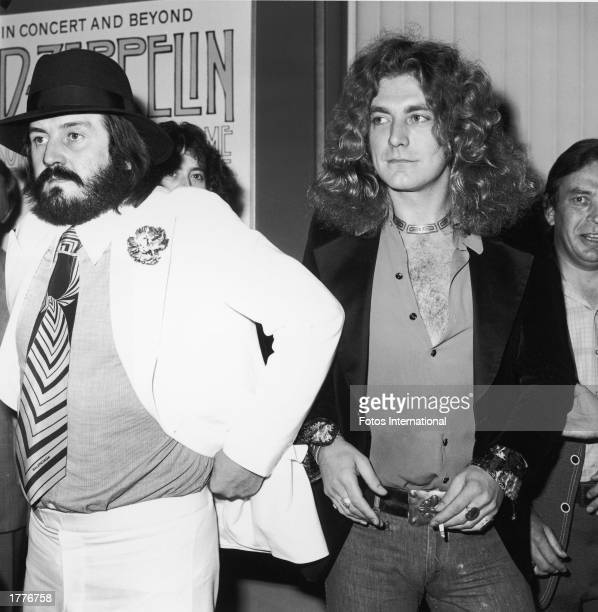 British singer Robert Plant lead singer of the rock band Led Zeppelin holds a lit cigarette while standing with John Bonham the band's drummer who...