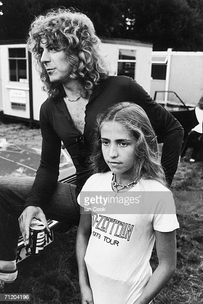 British singer Robert Plant of the rock and roll group Led Zeppelin stands, a can of 7UP soda in one hand, with his daughter Carmen, who wears a 1973...