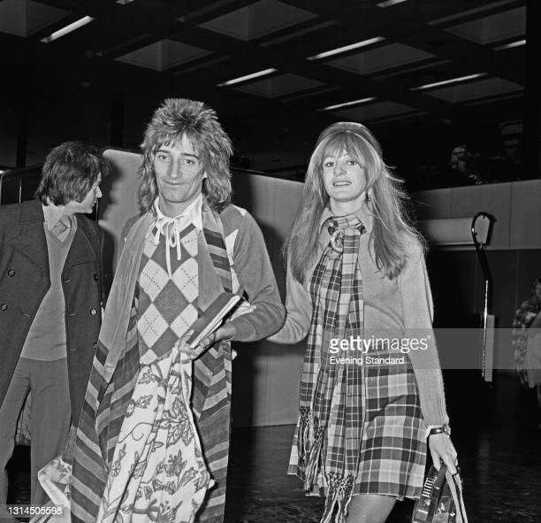 British singer Rod Stewart of the rock band Faces at Heathrow Airport in London with his girlfriend Dee Harrington, UK, 24th January 1974. They are...