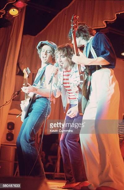 British singer Rod Stewart on stage at the Olympia London December 1976 With him are guitarists Jim Cregan and Gary Grainger