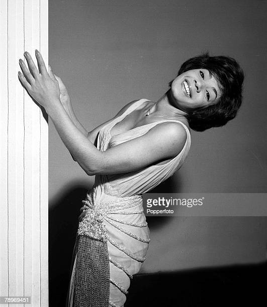 British singer Shirley Bassey poses in an elegant beaded dress with her head tilted back in a 1960 studio portrait