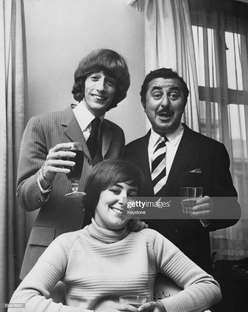 British singer, songwriter and musician Robin Gibb (1949 - 2012, left), formerly of the Bee Gees, with his first wife, Molly, and managing director of NEMS Enterprises, Vic Lewis (1919 - 2009). They are celebrating Gibb's signing of a contract with NEMS, 5th September 1969.