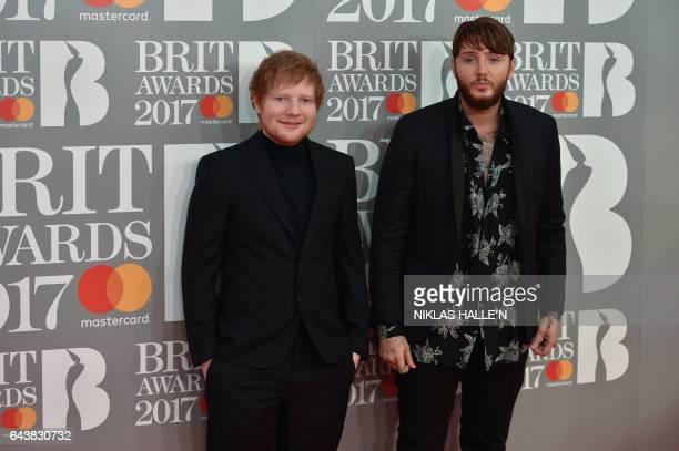 British singer song-writers Ed Sheeran and James Arthur pose on the red carpet arriving for the BRIT Awards 2017 in London on February 22, 2017. /...