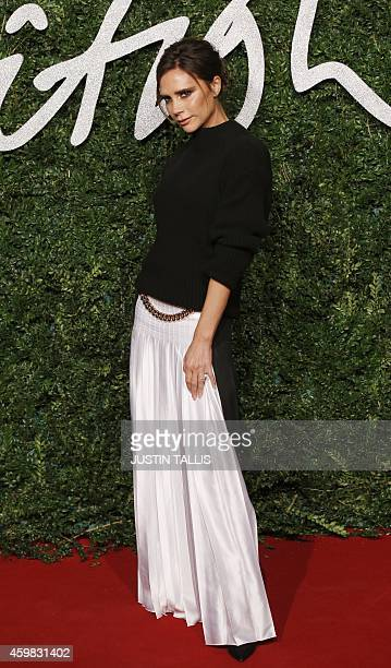 British singer Victoria Beckham poses for pictures on the red carpet upon arrival to attend the British Fashion Awards 2014 in London on December 1...