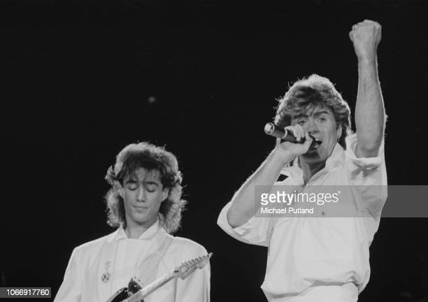 British singers and musicians George Michael and Andrew Ridgeley of Wham perform live on stage together during the pop duo's 1985 world tour in...