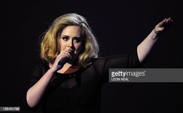 British singer-songwriter Adele accepts the British Female Solo Artist award at the BRIT Awards 2012 in London on February 21, 2012. AFP PHOTO / LEON...