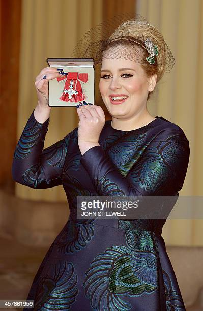 British singer-songwriter Adele Adkins holds her medal after being appointed a Member of the Order of the British Empire for services to music...