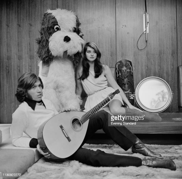 British singersongwriter and musician Barry Gibb holding a lute with his girlfriend Linda Gibb and a giant stuffed dog toy UK 25th January 1969