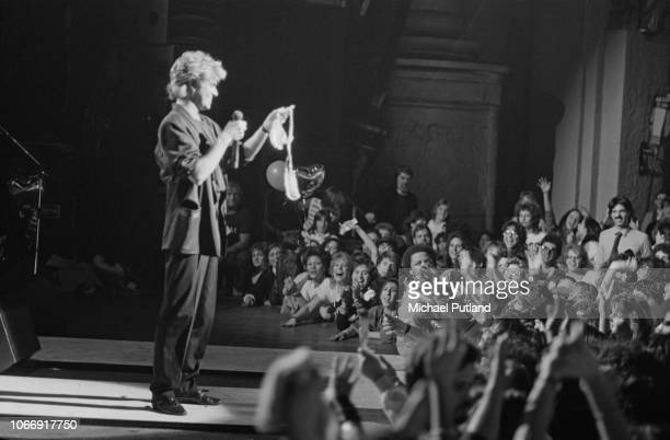British singer-songwriter and musician George Michael of pop duo Wham! holds up a bra thrown onstage during a concert at the Beacon Theatre in New...