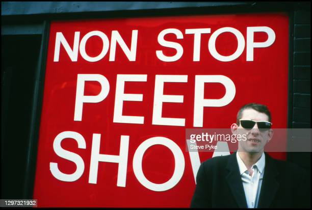 British singer-songwriter and musician Shane MacGowan by the entrance of a 'non-stop peep show' on Old Compton Street in London, England, 1987.
