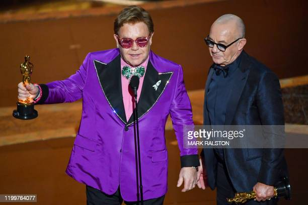 British singersongwriter Elton John and British lyricist Bernie Taupin accept the award for Best Original Song for Love Me Again 'Rocketman' during...