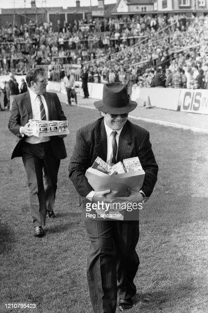 British singer-songwriter Elton John, dressed in a pin stripe suit and a fedora, giving out Easter eggs to fans attending the First Division match...
