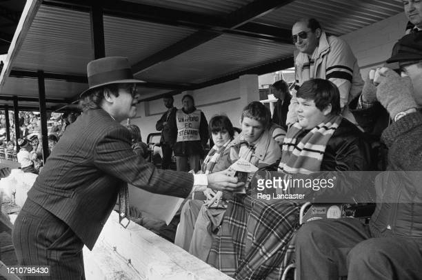 British singer-songwriter Elton John, dressed in a pin stripe suit and a fedora, giving out Easter eggs to disabled fans attending the First Division...