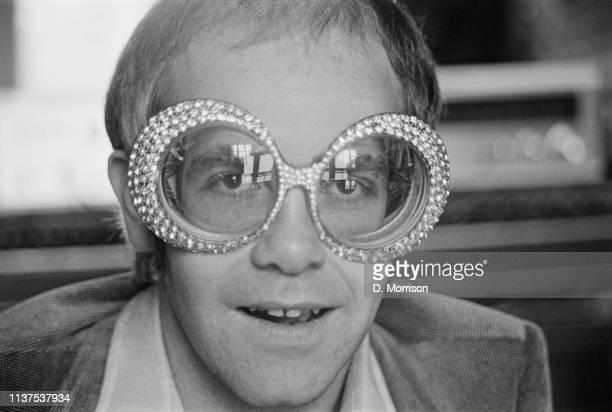 British singer-songwriter Elton John wearing a pair of his flamboyant trademark spectacles, 12th September 1974.