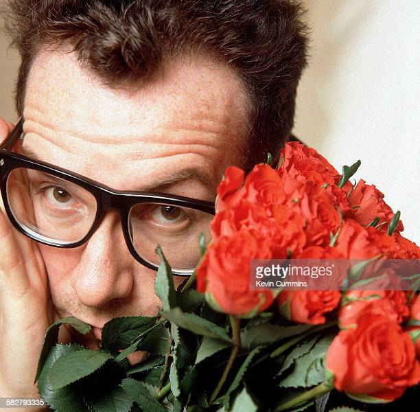 British singersongwriter Elvis Costello holding a bouquet of roses circa 1985